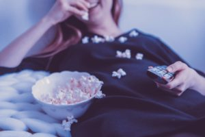 Woman watching TV eating popcorn in her pyjamas