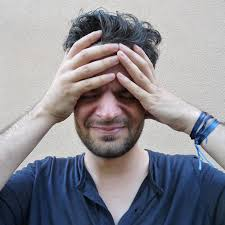 Picture of a man with his head in his hands looking stressed
