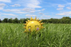 Picture of an inflatable yellow sun in a field of grass with a blue sky in the background with white fluffy clouds